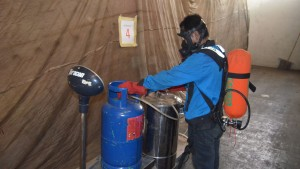 Releasing Methyl Bromide into Fumigation Enclosure, donning full safety gears.